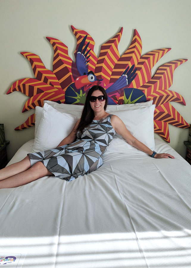 Woman sitting on a bed in an Art of Animation Lion King family suite