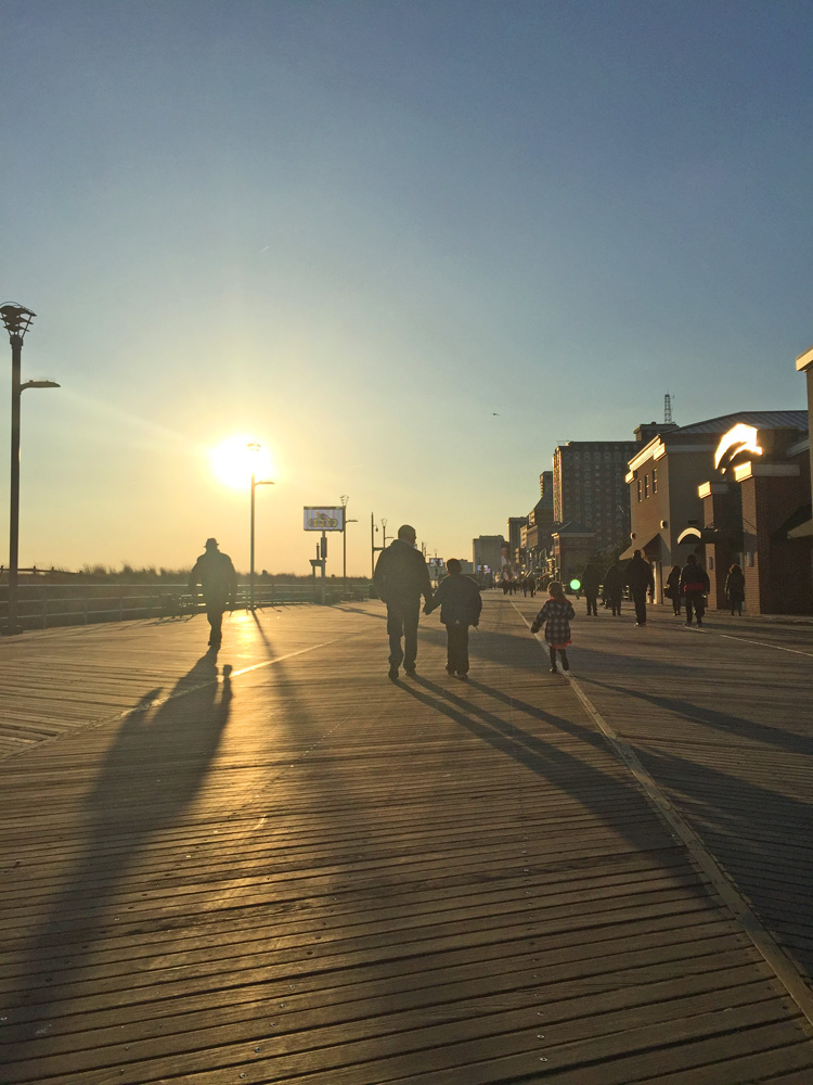 People silhouetted against the sun on the Atlantic City Boardwalk
