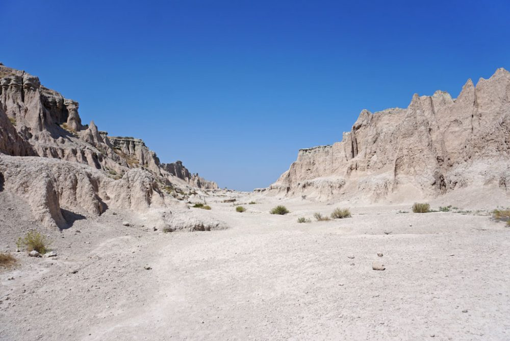 Flat canyon bottom with chalky dirt and low, naturally striped walls under bright blue skies