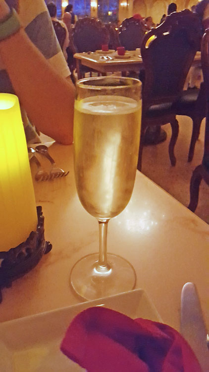 Glass of champagne on the table at Disney's Be Our Guest dinner
