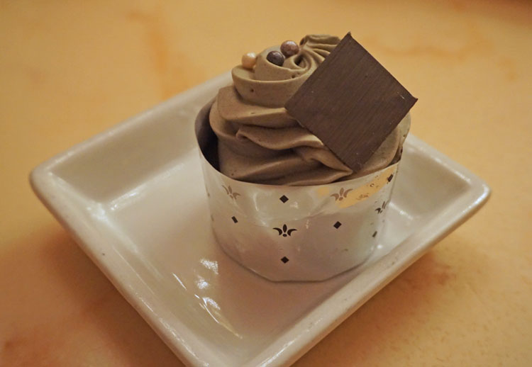 """Cupcake with chocolate embellishment and """"grey stuff"""" frosting at Disney's Be Our Guest restaurant in the Magic Kingdom"""