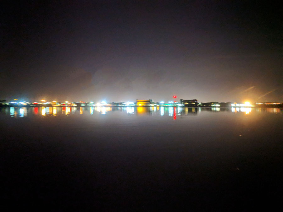 Blurry view of city lights reflecting on water