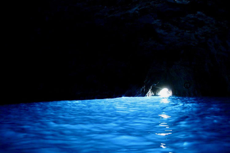 Blue light shining from the water in the Blue Grotto
