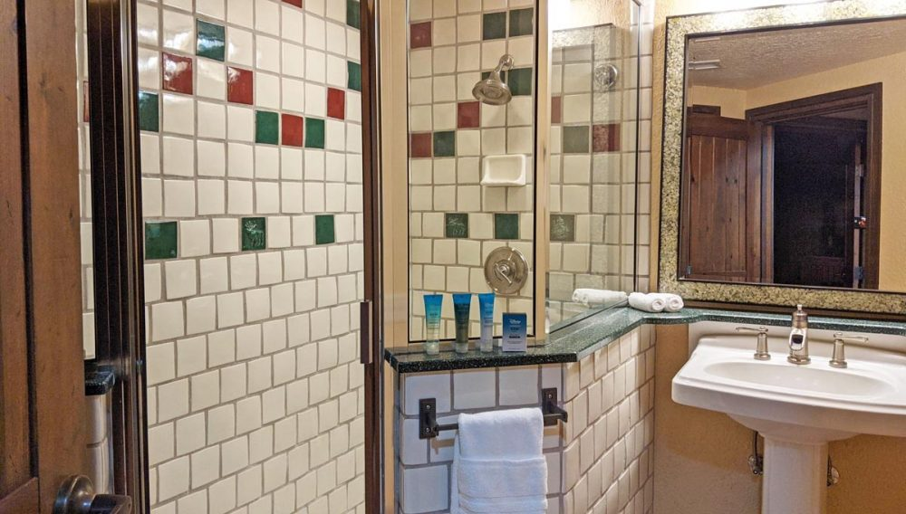 Tile and glass shower enclosure, mirror, and pedestal sink in a Boulder Ridge one-bedroom villa bathroom