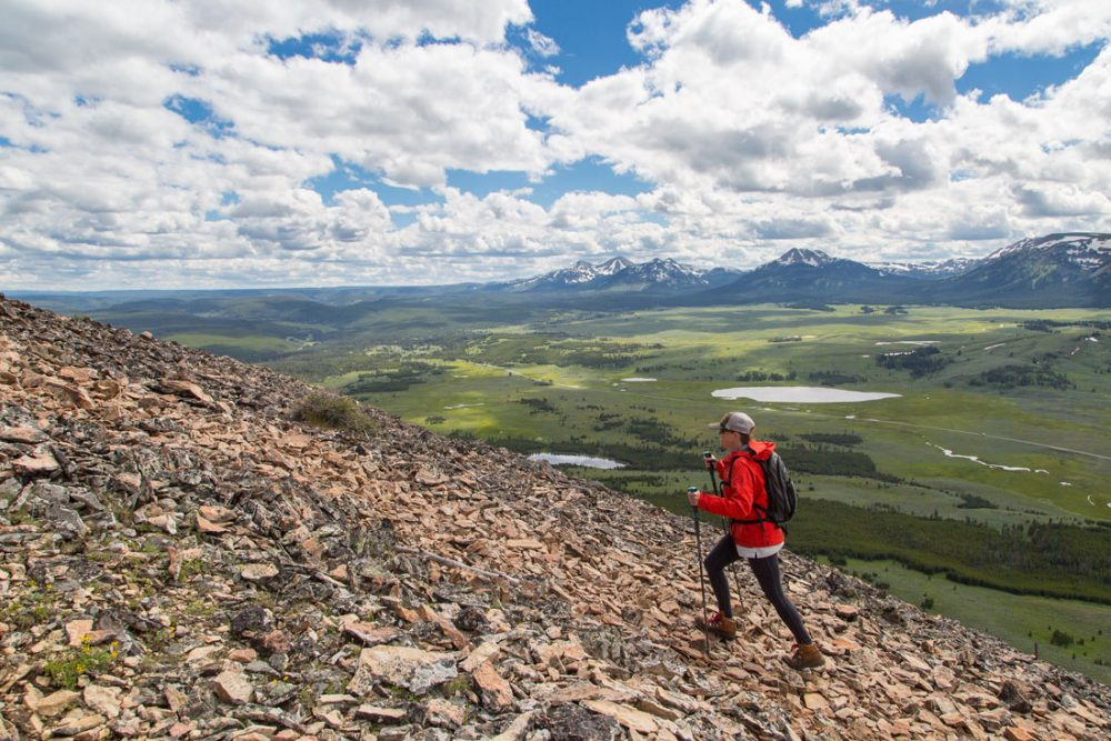 A hiker climbs a rocky ridge near the top of a mountain, with partly cloudy skies above and rolling green valleys below