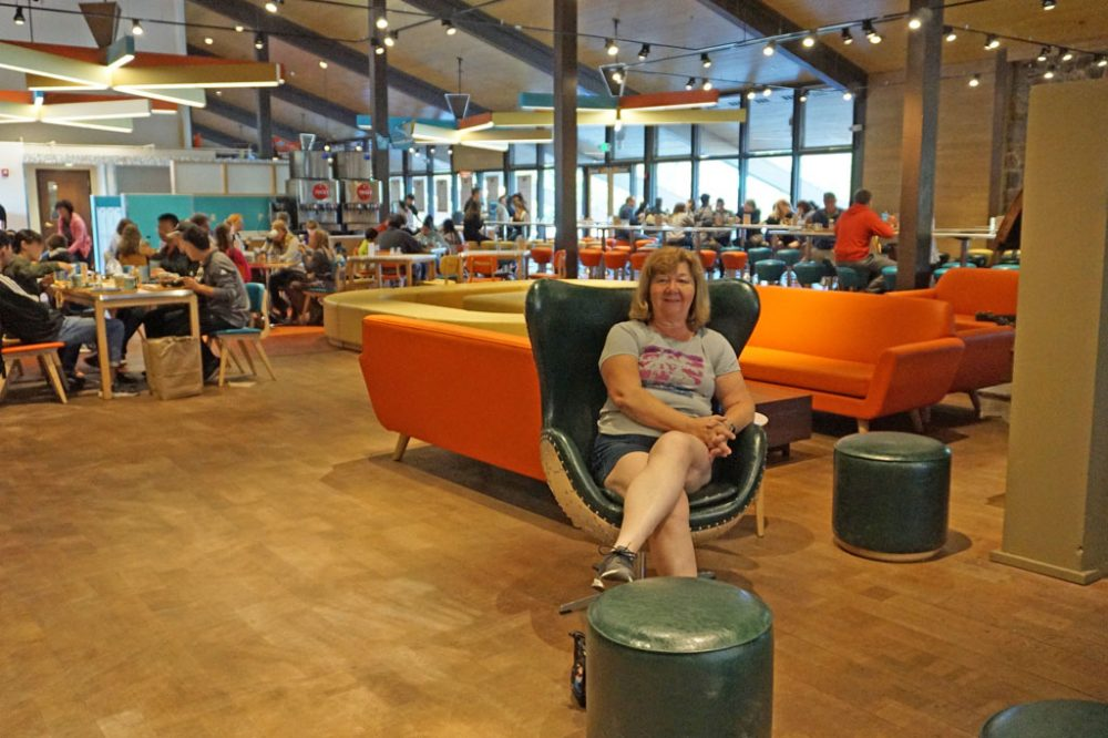 White woman seated on a chair inside a large open cafeteria with retro styling