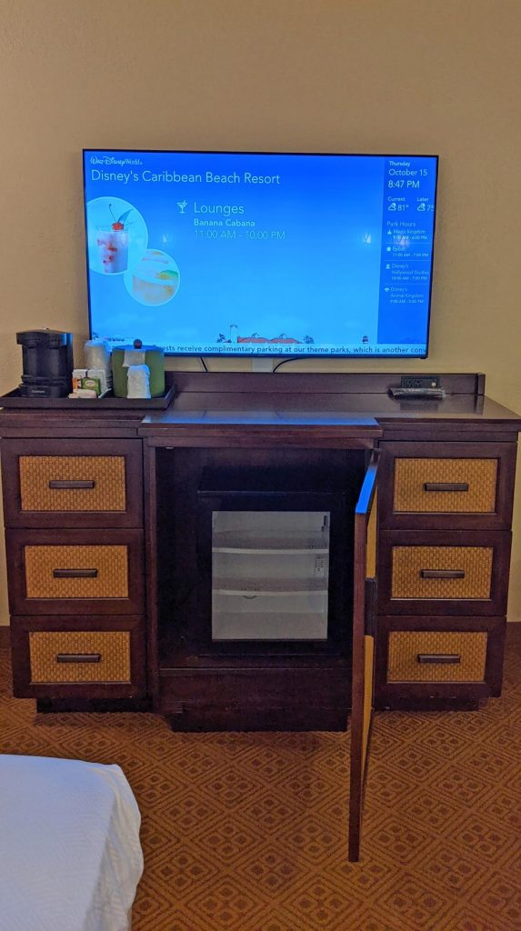 Dresser with tv, coffee pot, and refrigerator inside a guest room at Disney's Caribbean Beach Resort