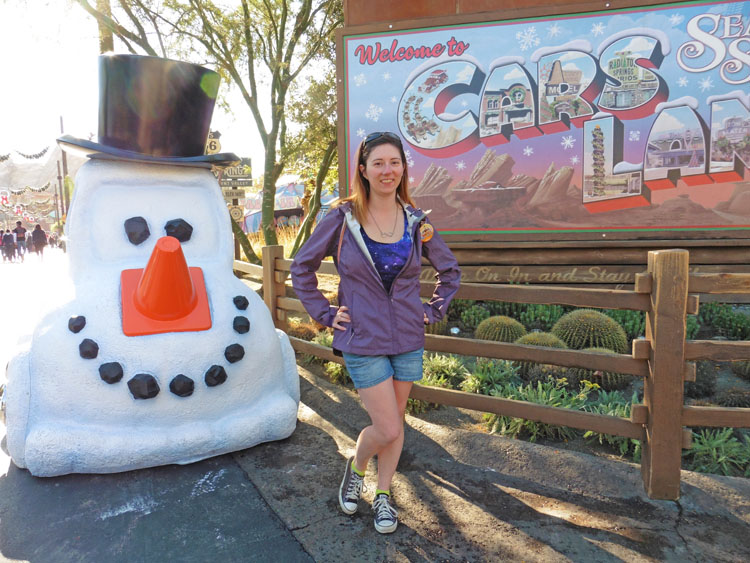 Woman posing with Christmas decorations in California Adventure's Cars Land