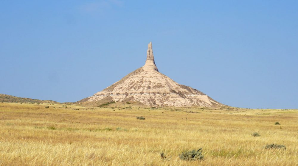 Cone-shaped rock formation towering above rolling yellow grasses and beneath a blue sky