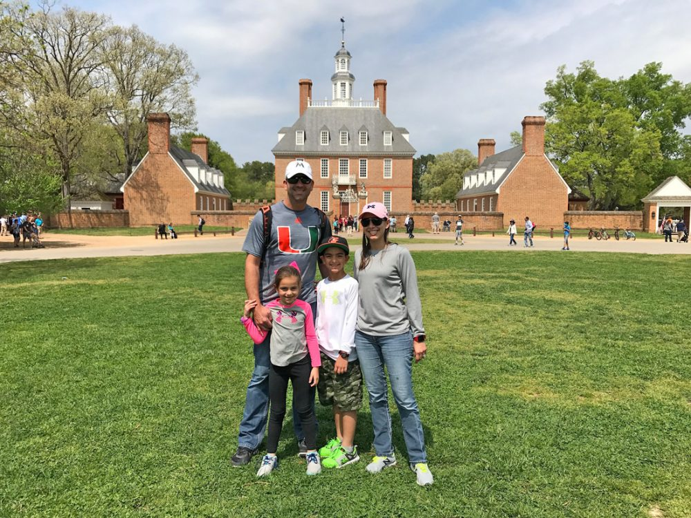 Family posing in front of historic buildings in Colonial Williamsburg