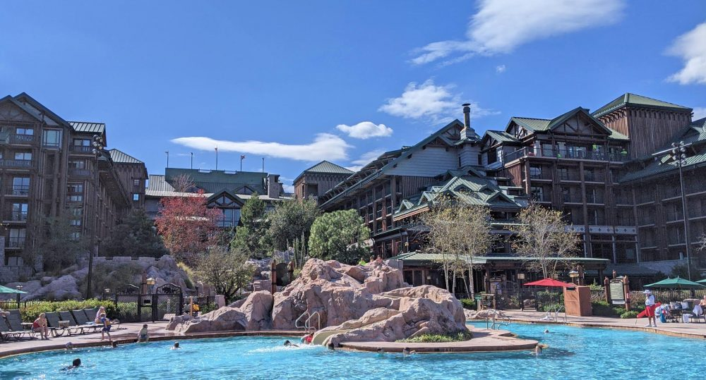 Pool with a waterslide weaving through boulders with a multi-story log lodge behind it