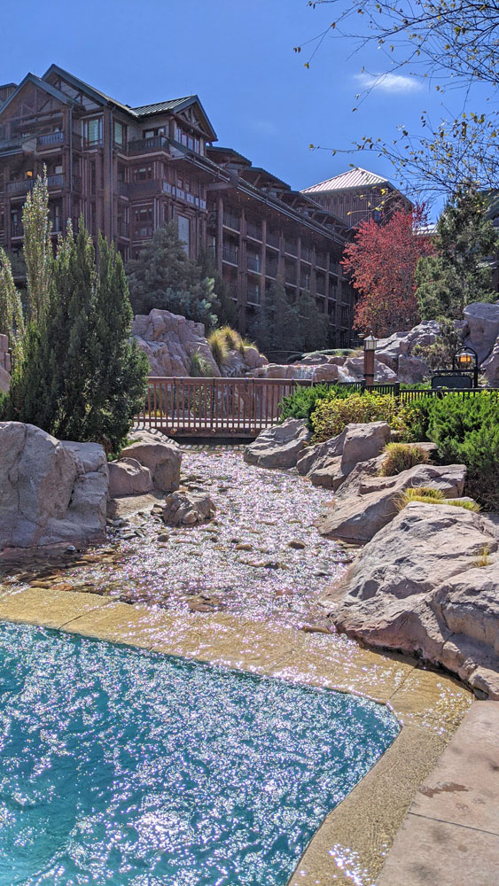 Pool next to boulders with an artificial stream flowing into it