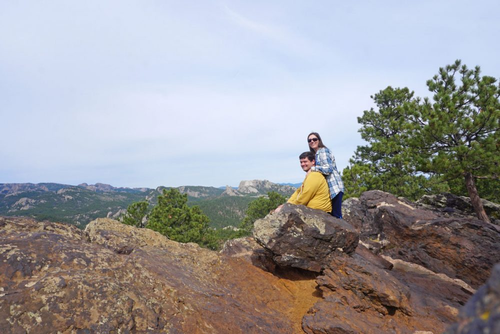 Couple posing in front of Mount Rushmore at the Norbeck Overlook
