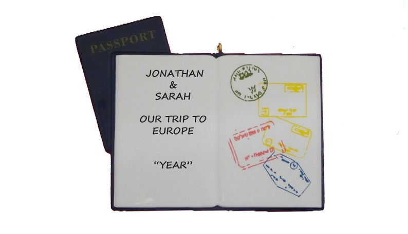 Open passport shaped ornament with custom inscription and colorful entry stamps