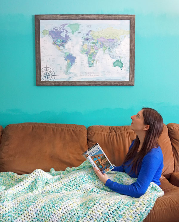 Woman on a couch looking up at a framed pushpin travel map.