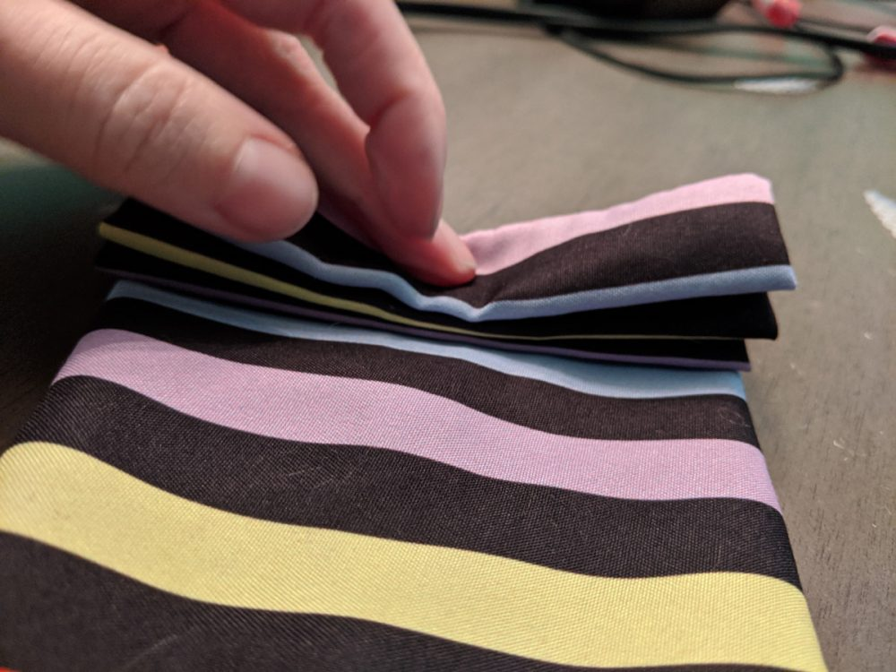 Folding striped fabric into a Minnie Mouse bow