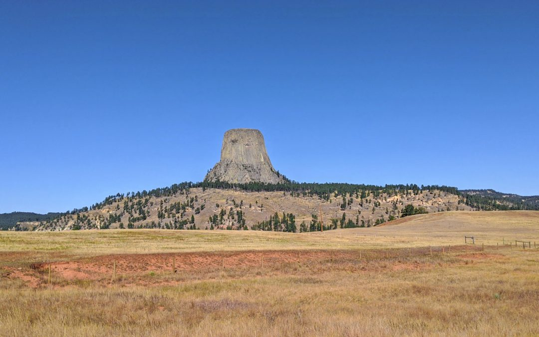 Landscape view of Devils Tower National Monument towering above the prairie grass