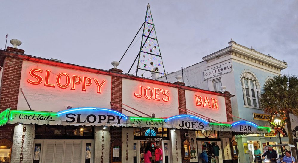 """Pedestrians walk in front of a building with awnings and """"Sloppy Joe's Bar"""" in neon lights on Duval Street in Key West"""