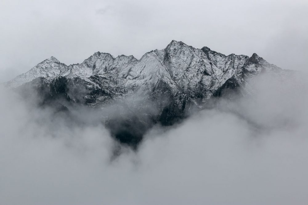 Black and white photo of a mountain peak shrouded by fog