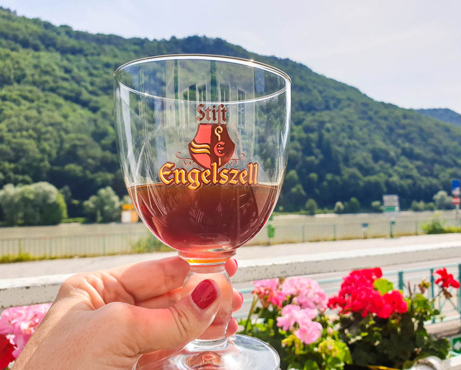 Glass of Engelzell Abbey beer with mountains in the background