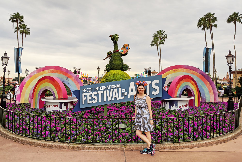 Woman posing in front of the Epcot International Festival of the Arts sign