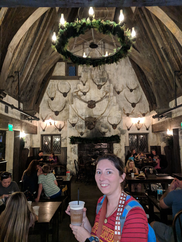 Woman holding a frozen butterbeer at the Three Broomsticks