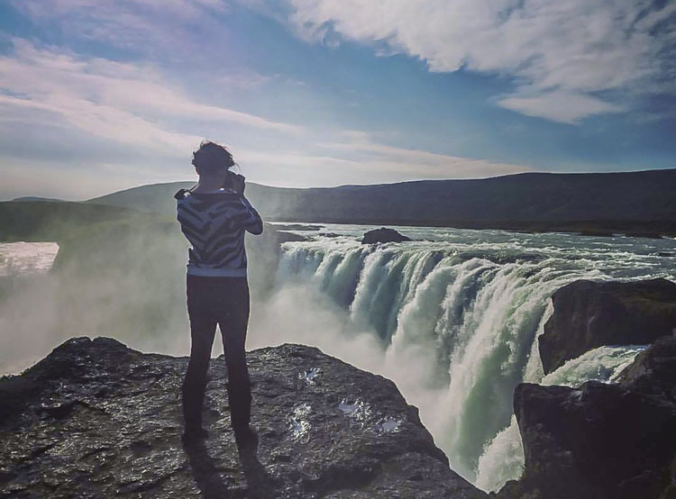 Woman standing with a view of Godafoss