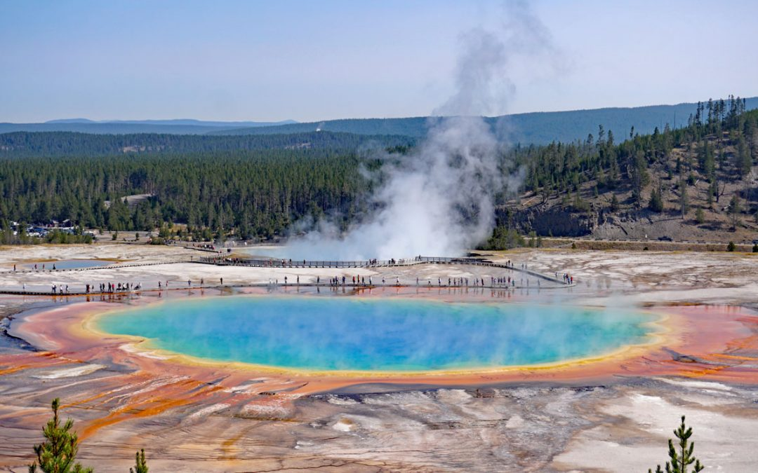 Rainbow colored pool called Grand Prismatic Spring under clear blue skies
