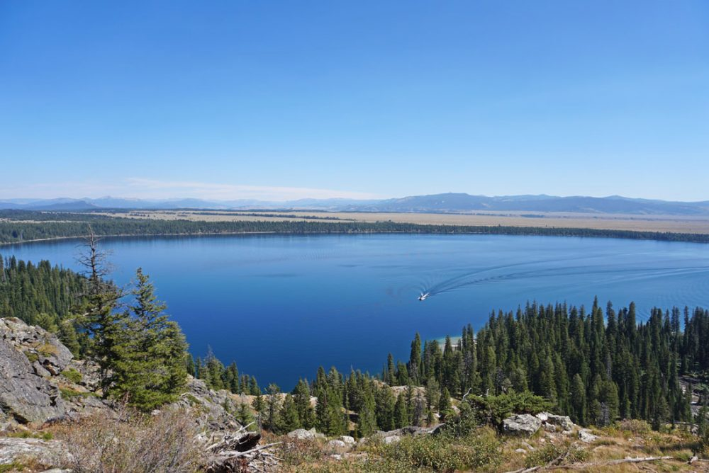 Elevated view of a large mountain lake with a small boat making a wake and grassy fields beyond it under blue skies