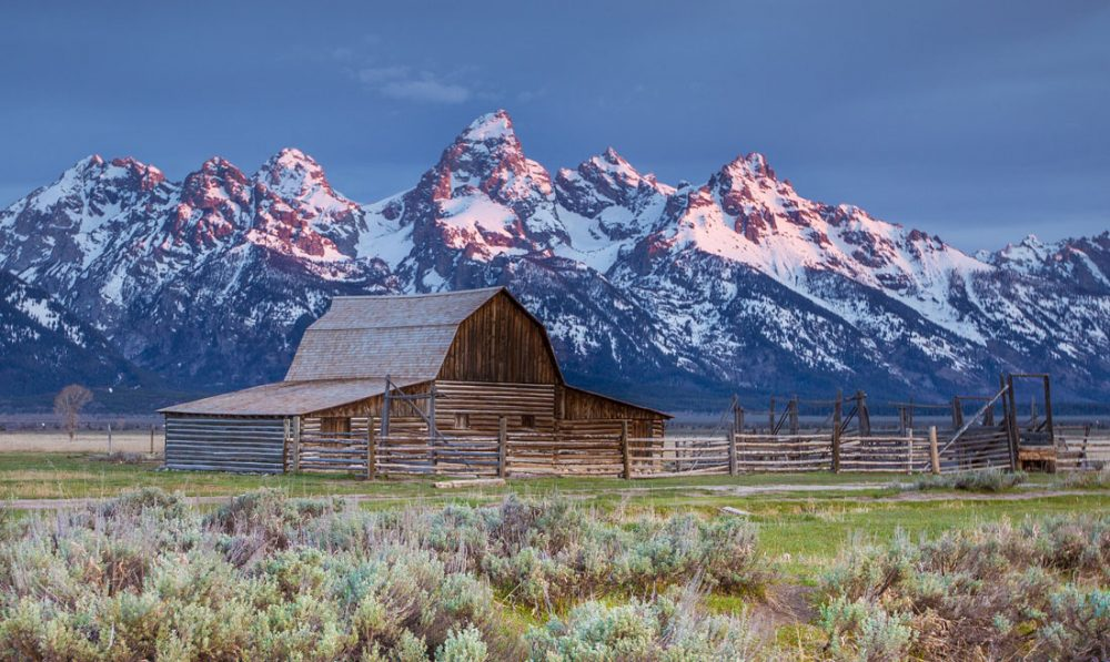 Photo of a small barn with the towering Grand Teton peaks in the background