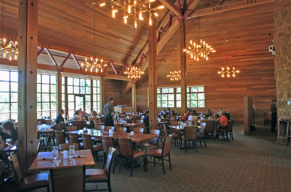 Wood framed dining room with vaulted ceilings and chandeliers with guests seated at tables eating