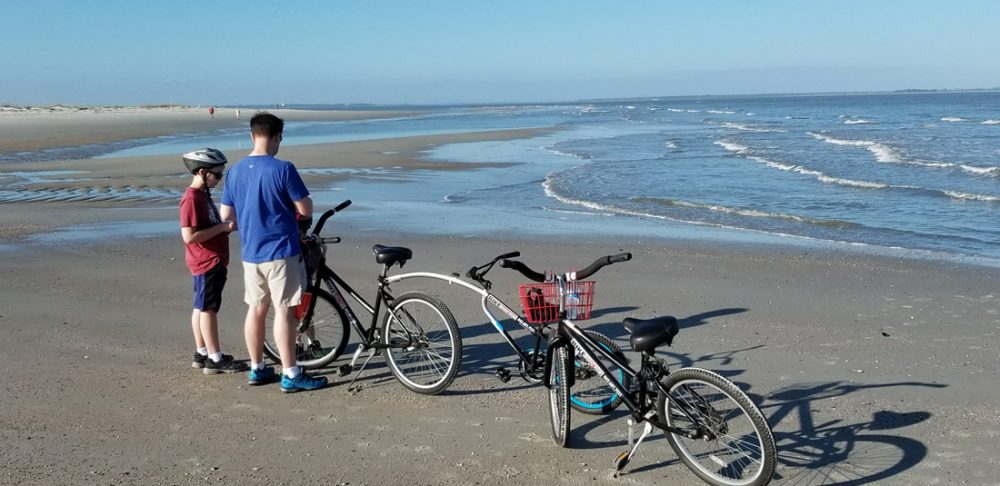 Father and son standing by bikes on a beach on Hilton Head Island