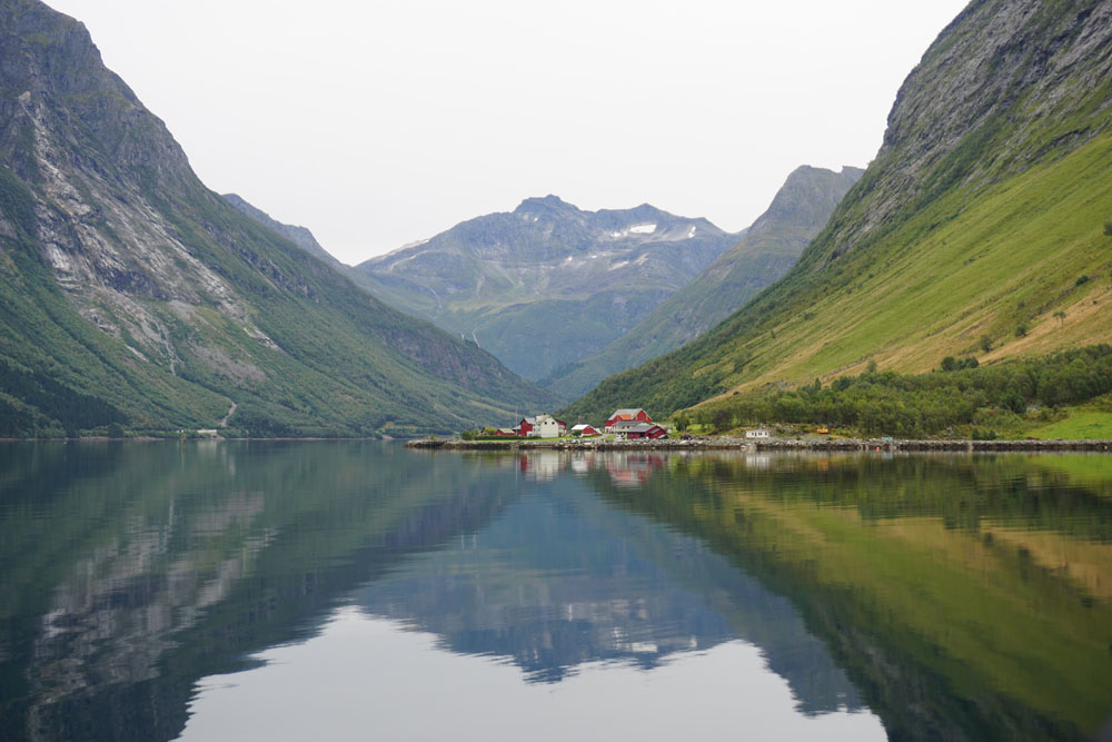 Mountains reflected in water in the Hjorundfjord on a day trip from Alesund, Norway