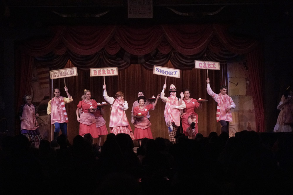 Performers and servers on stage at the Hoop Dee Doo with trays of strawberry shortcake