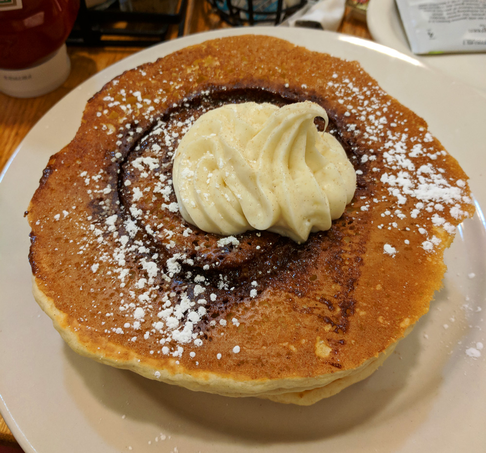 Large stack of pancakes with a swirl of frosting
