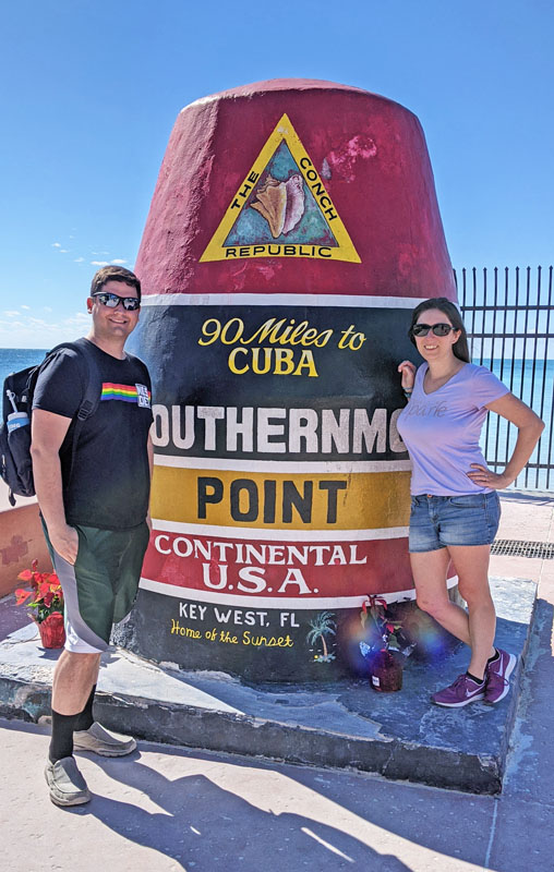 """White man and woman smiling for the camera next to a large buoy that says """"southernmost point continental US"""" in Key West, Florida"""