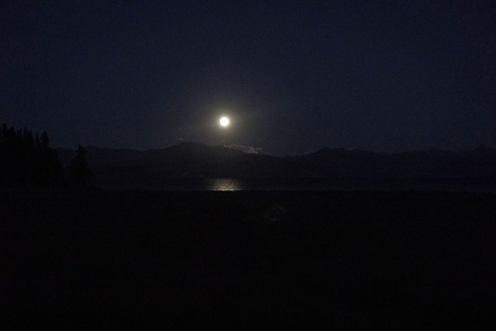 Full moon reflecting on a lake with mountains in the background