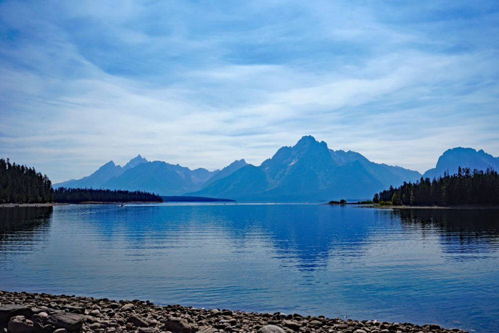 Photo of mountain peaks reflecting on the calm waters of Jackson Lake in Grand Teton National Park