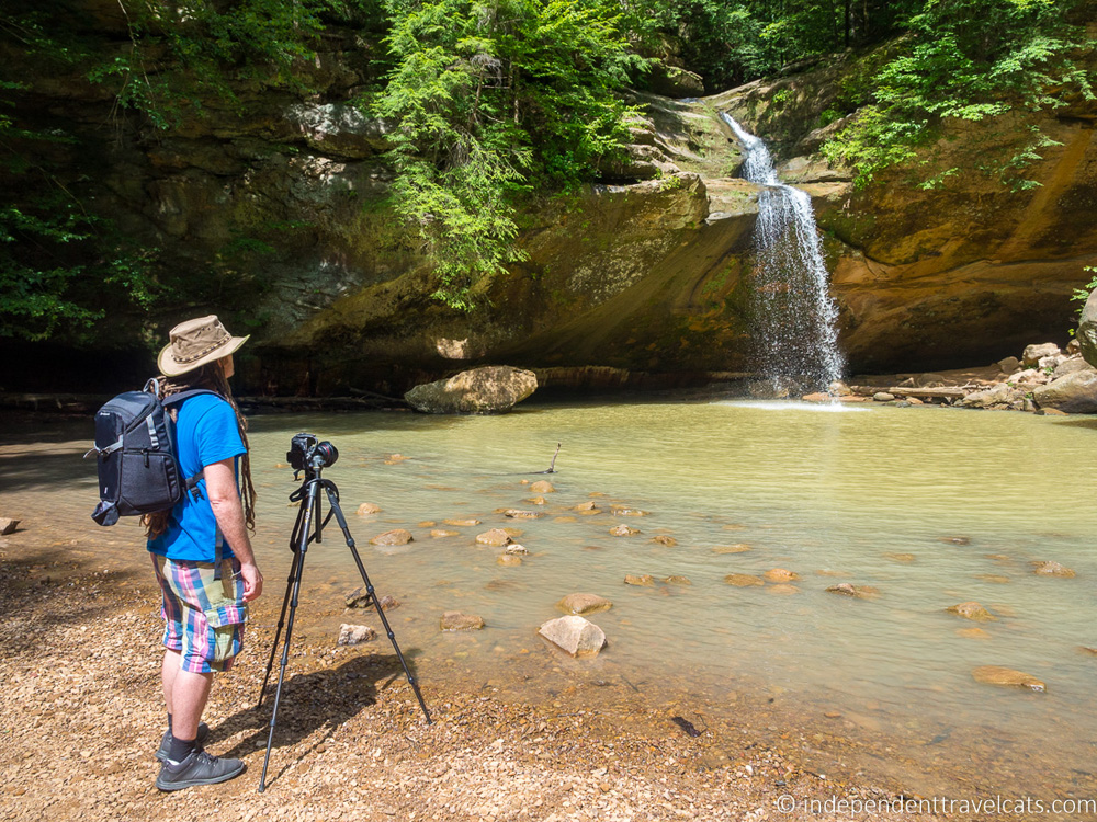 Man with a tripod standing near a small waterfall