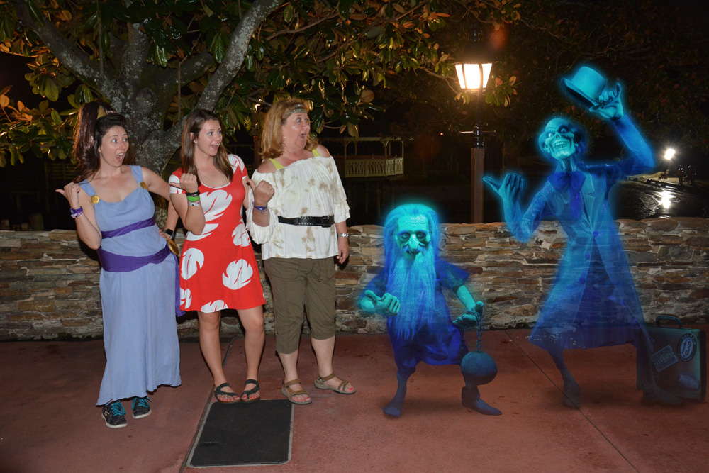 Women dressed as Megara, Lilo, and a pirate hitchhiking with ghosts in a special PhotoPass Magic Shot