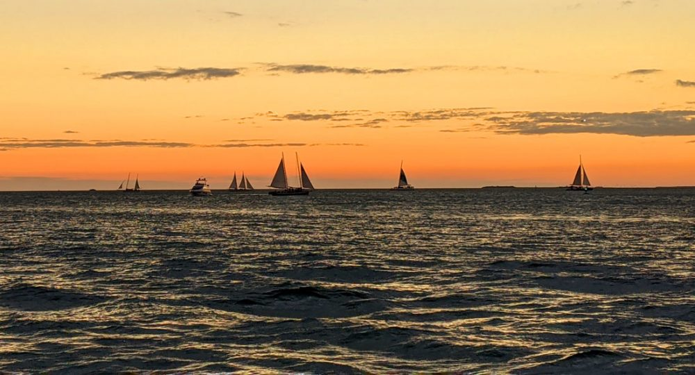 Orange skies over calm seas with sailboats silhouetted against the sunset viewed from Mallory Square in Key West
