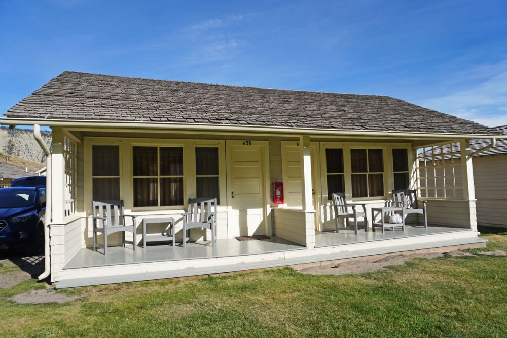 Duplex beige cabin with lawn chairs and tables on a divided porch under blue skies