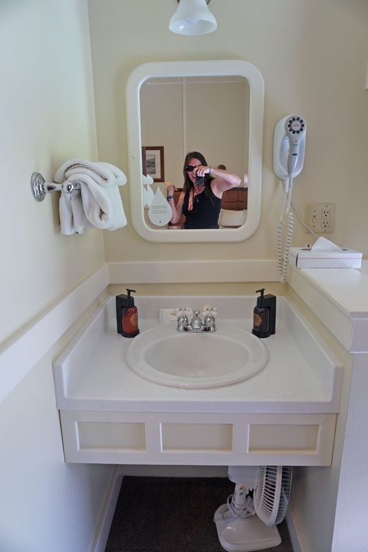 Small beige countertop with a sink and a wall-mounted mirror reflecting a white woman holding up a camera