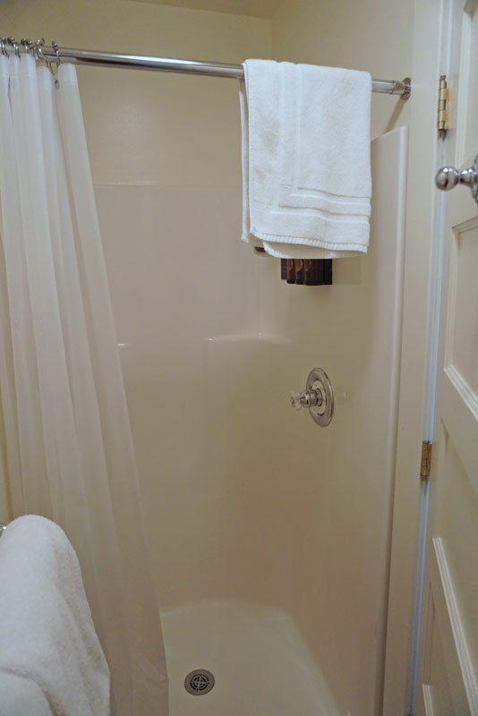 Ivory colored shower enclosure with a towel hanging off of the overhead bar