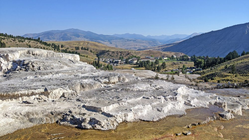 White travertine terraces at Mammoth Hot Springs with a hotel building in the background