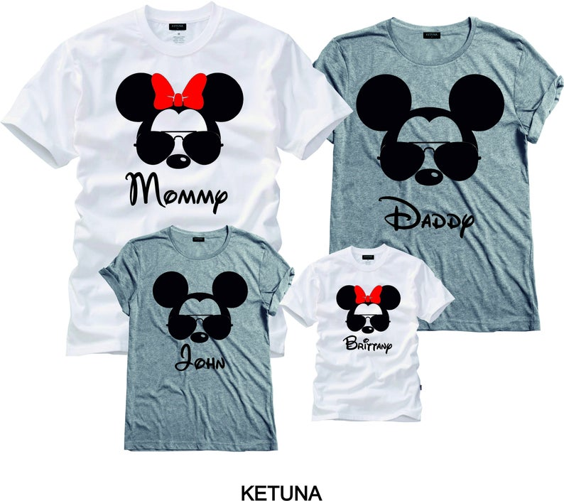 Four white and grey tshirts with Mickey or Minnie heads on them and personalized names below the icon