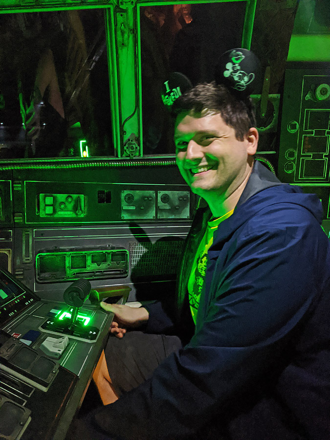 Man seated in a pilot seat in Millennium Falcon: Smuggler's Run at Disney World