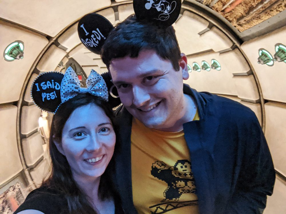 Man and woman in Mouse ears inside the Millennium Falcon