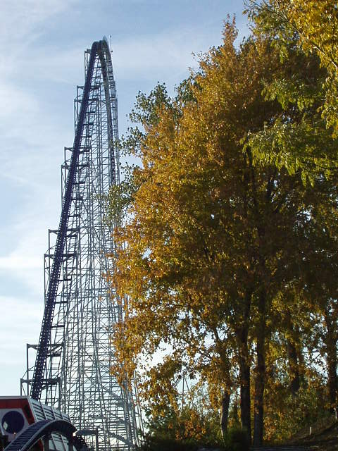 Tall steel roller coaster with fall foliage in the foreground