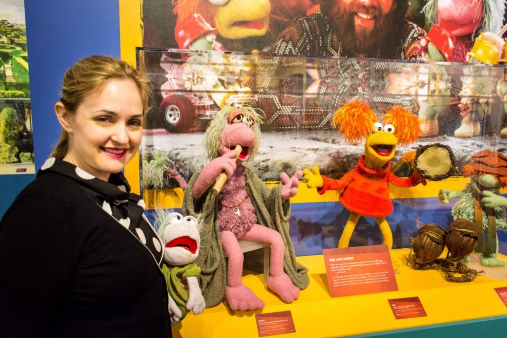 Woman posing with Muppets